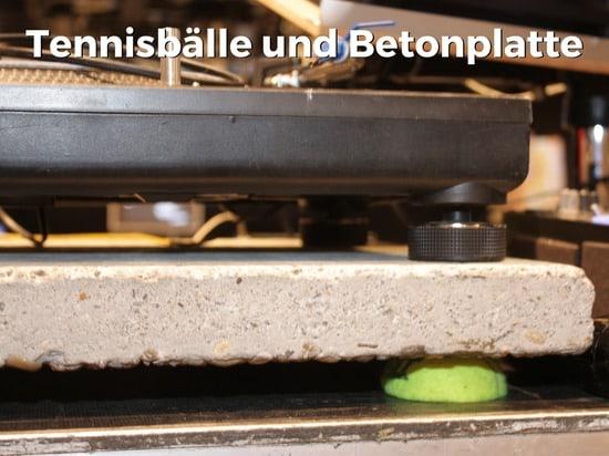 Plattenspieler auf Betonplatte und Tennisbällen